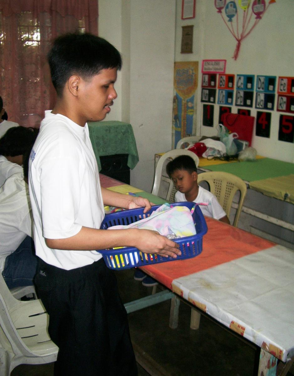 A boy carries his basket of materials to the table.