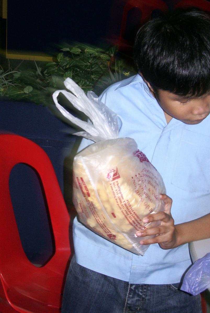 A boy carries a plastic bag of packages snacks.