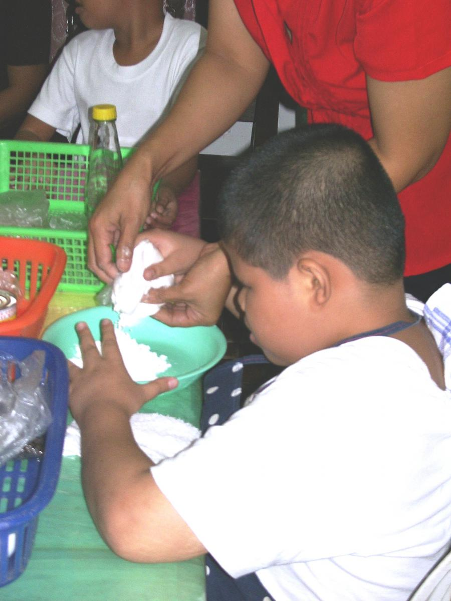 A boy practices handskills while preparing the dough.