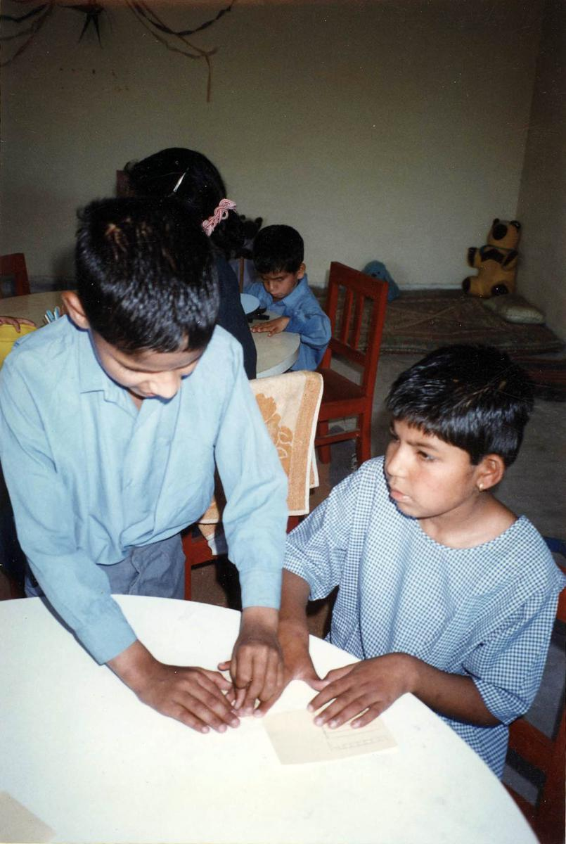 A boy reads braille with a classmate.