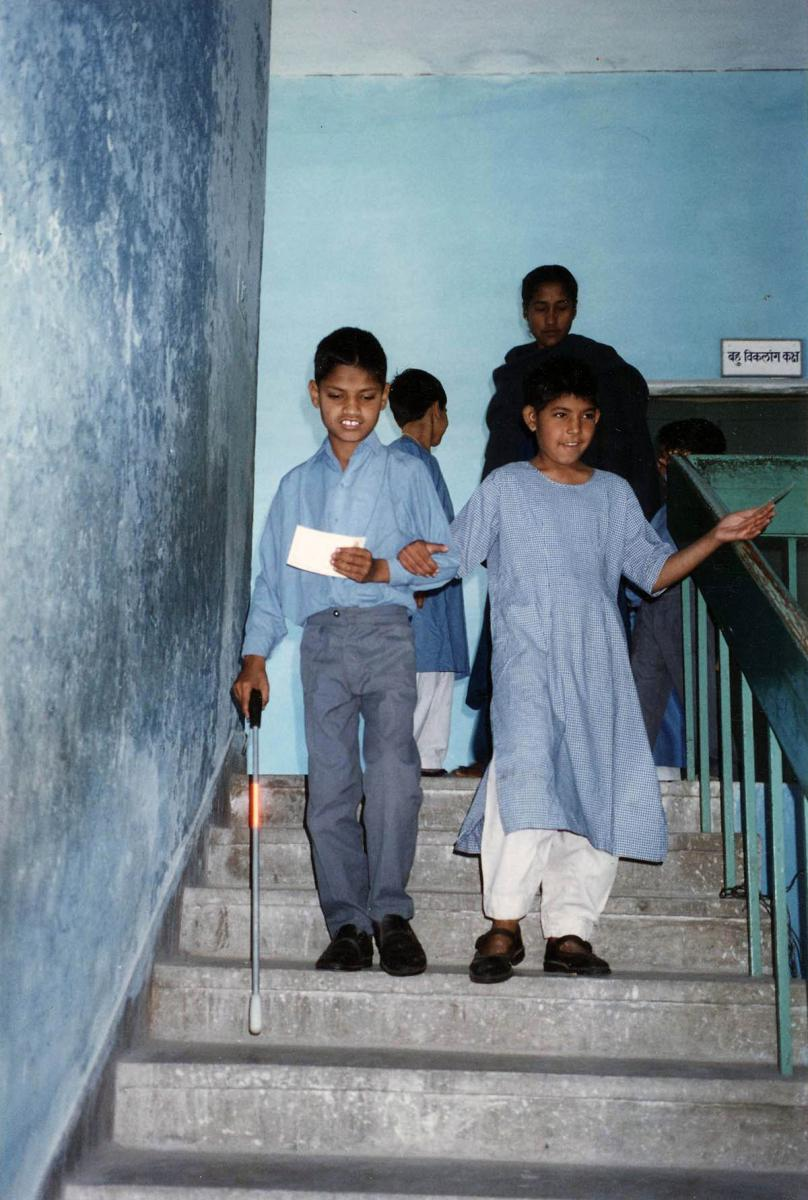 Students use a cane to walk down the stairs using a cane.