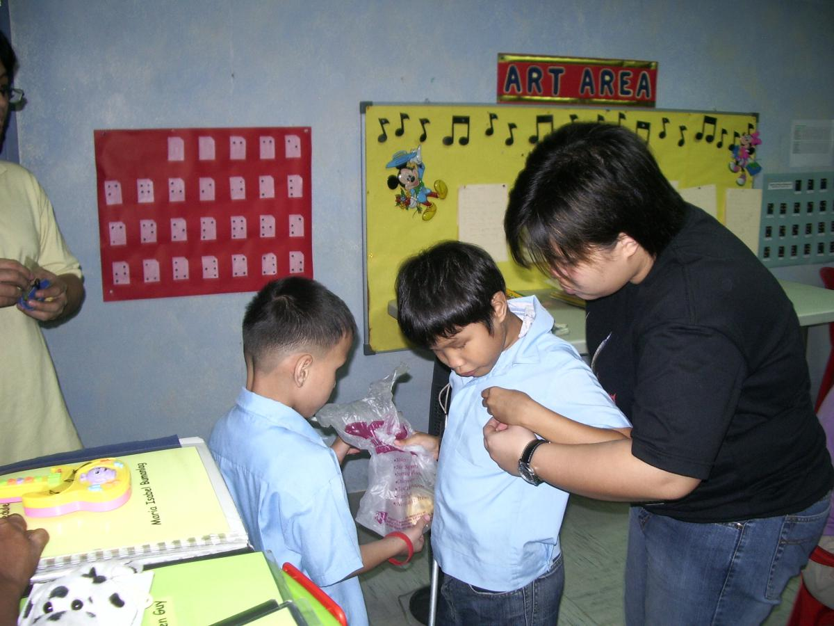 The teacher assists the boy to place the money in his shirt pocket.
