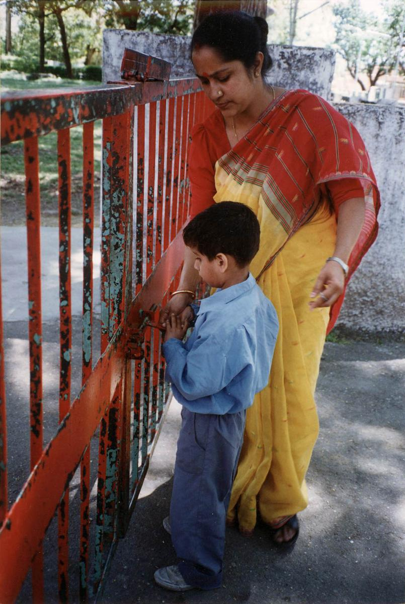 A young boy unlocks the gate.