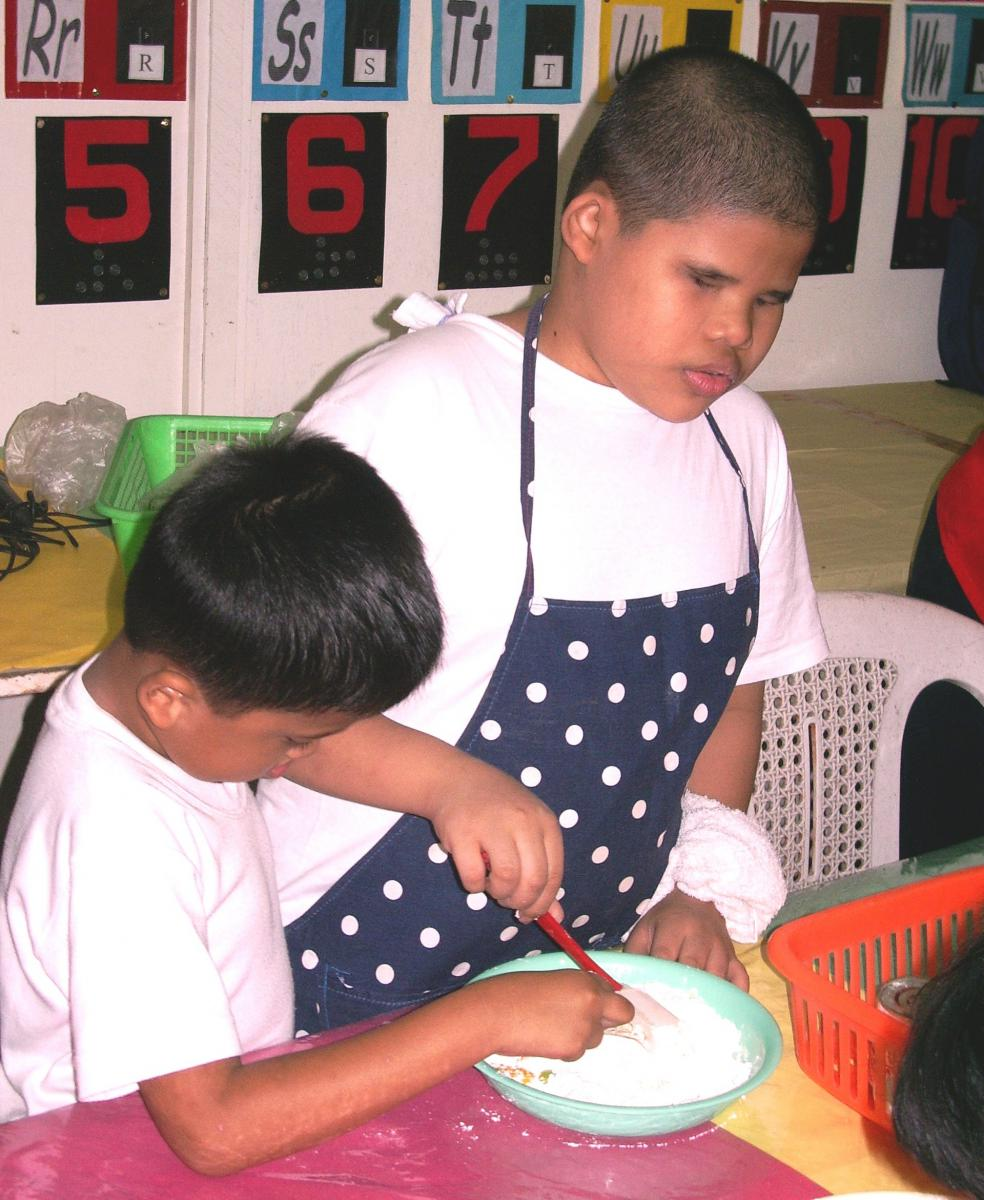 Two boys work together to prepare the dough.