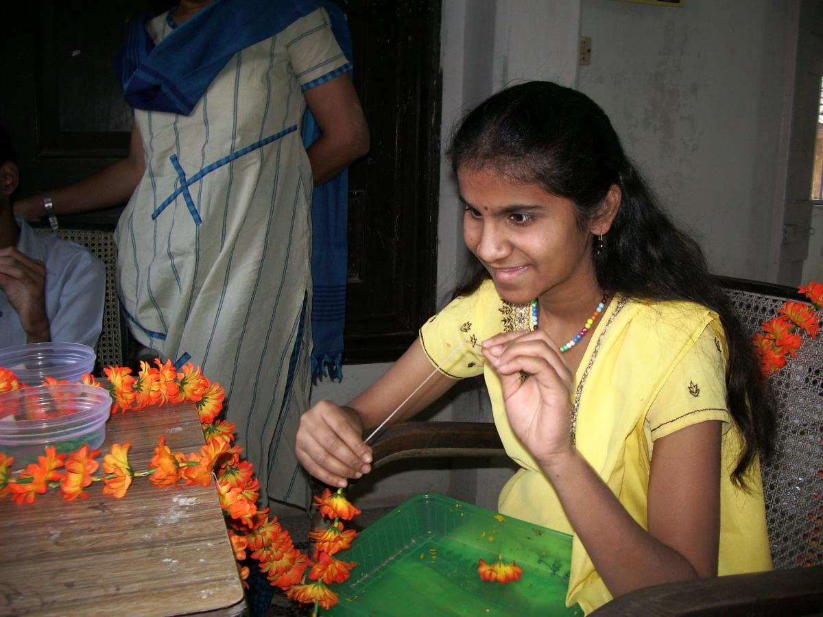 A girl makes a garland of flowers