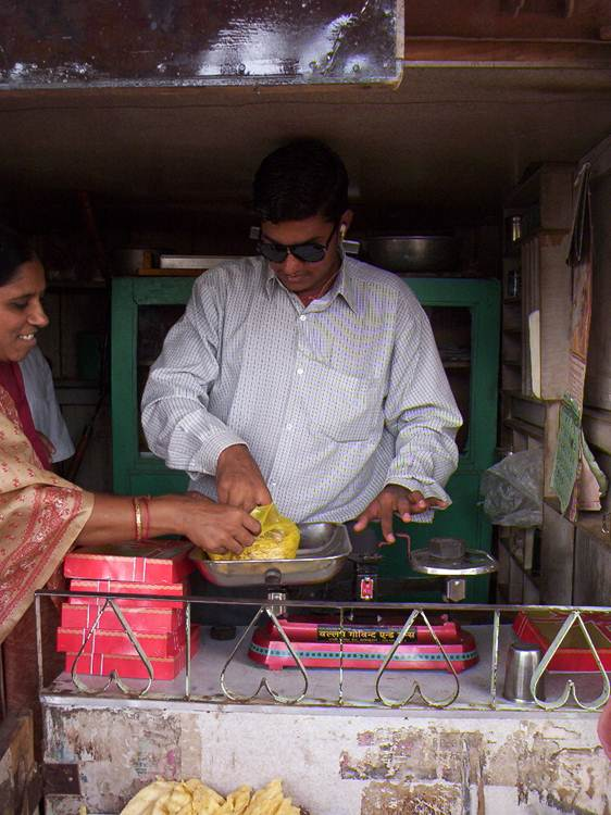 Photo of Rajesh weighing snacks in his shop