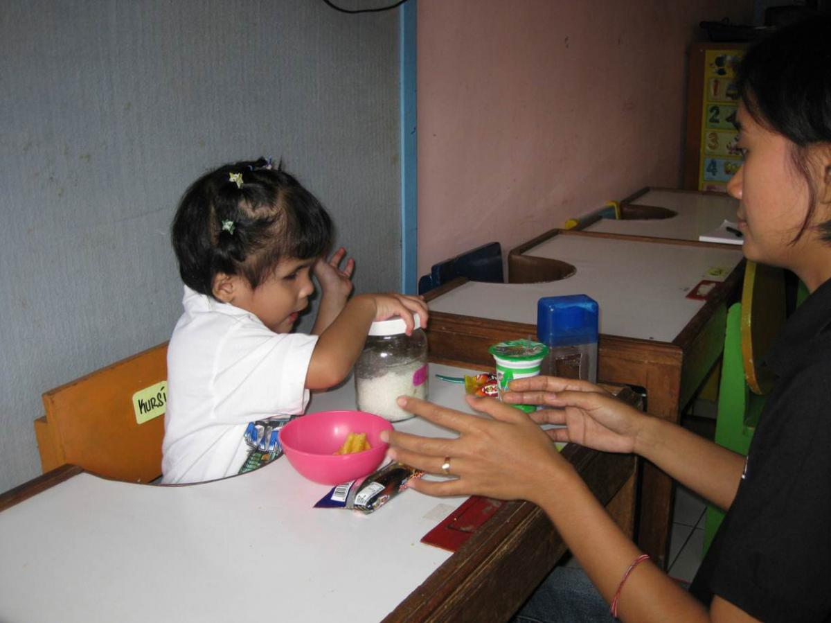 A girl spreads out her snack and prepares to open the jar of sugar.
