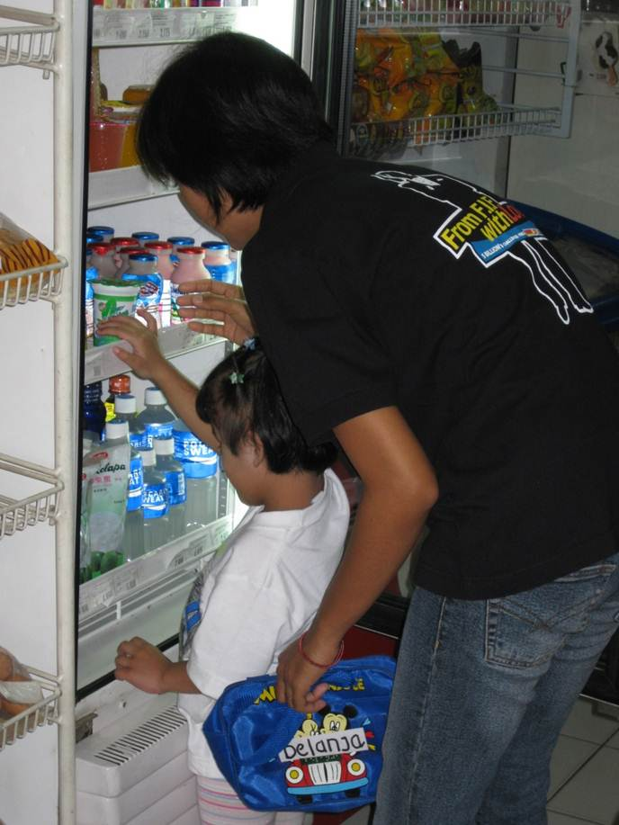 A girl reaches into a refrigerator to get choose a snack.