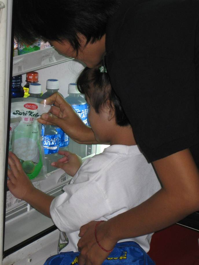 A girl and her teacher select a bag of snacks from the refrigerator.