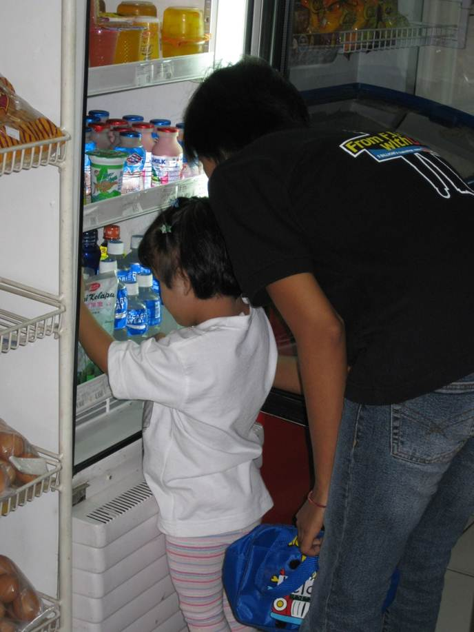 A girl lifts the snack she has selected out of the refrigerator.