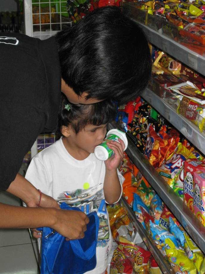 A girl stands in the snack aisle in a store.