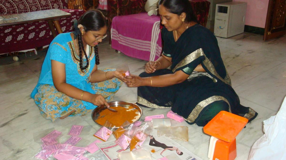 Teenage girl with hearing aids and glasses works with her mother to package curry powder.