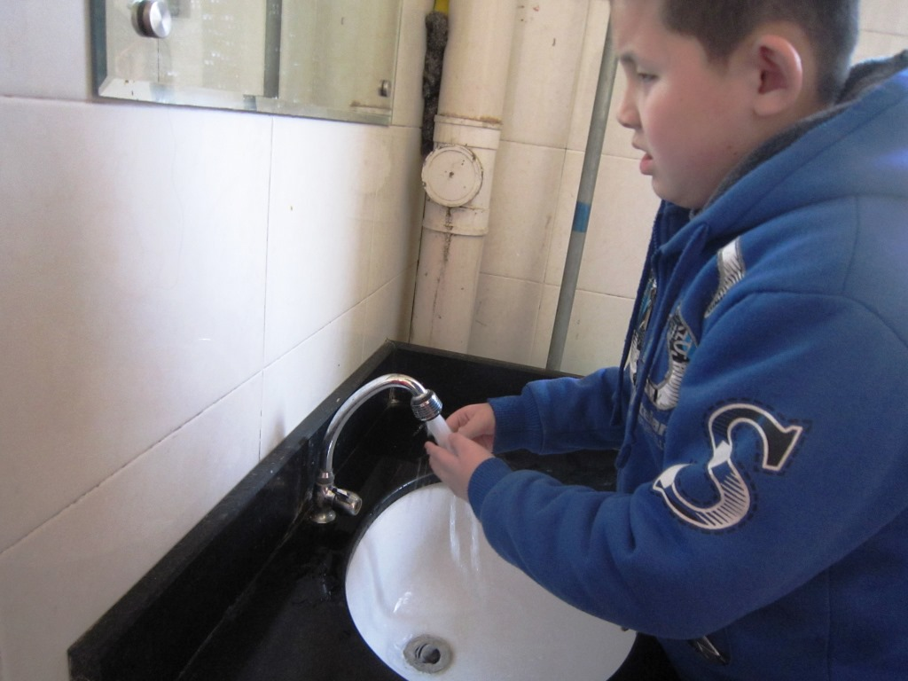 A boy washes his hands at the sink