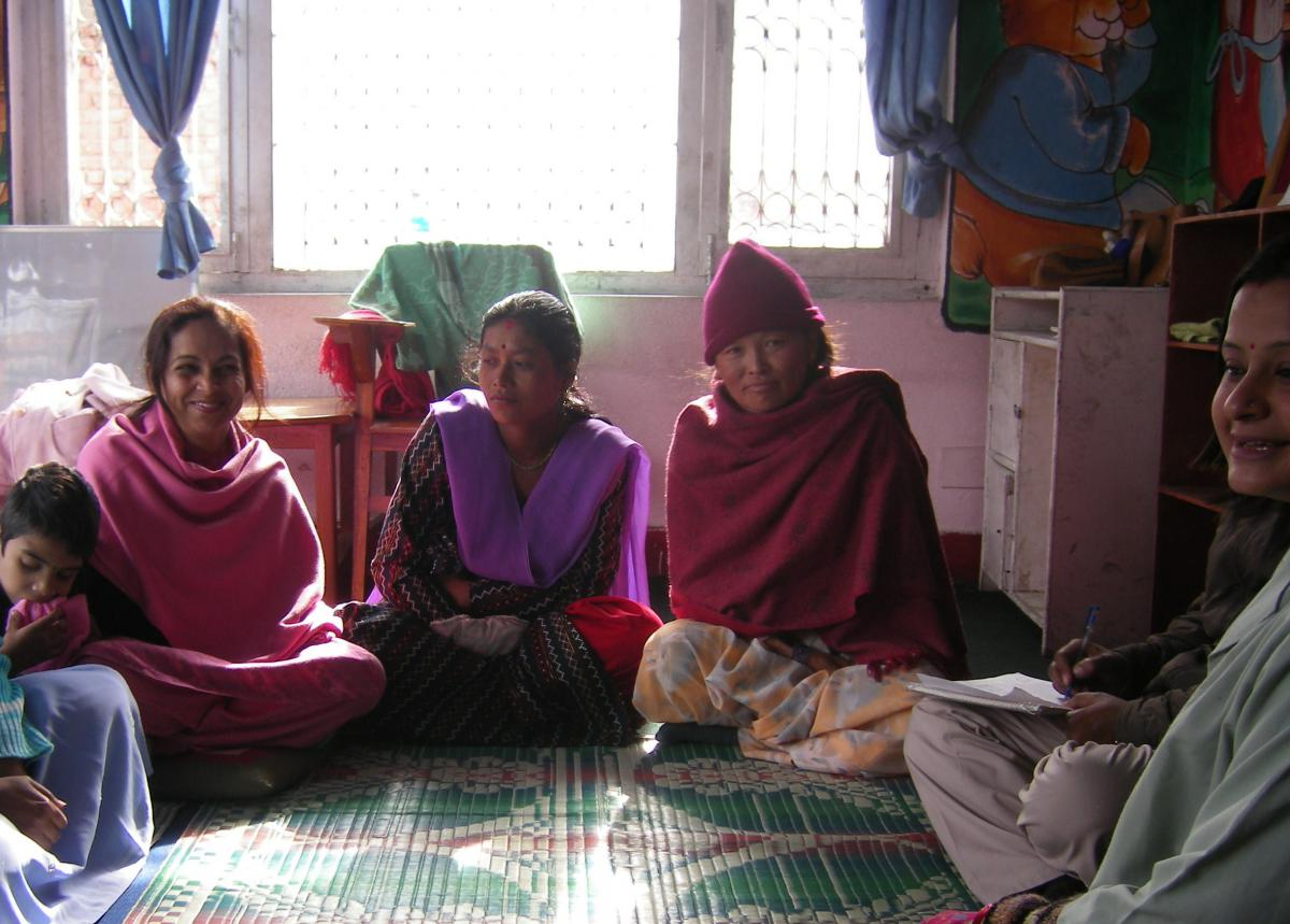 A gorup of women and a child sit on the floor.
