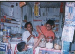 Photo of Surendar helping to serve sweets in his father's shop.