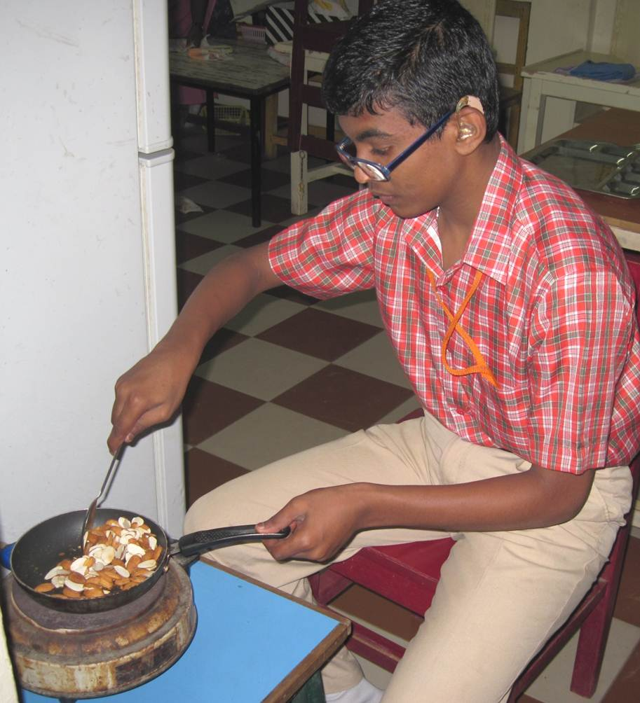 A boy wearing glasses and hearing aids stirs ingredients in a frying pan.