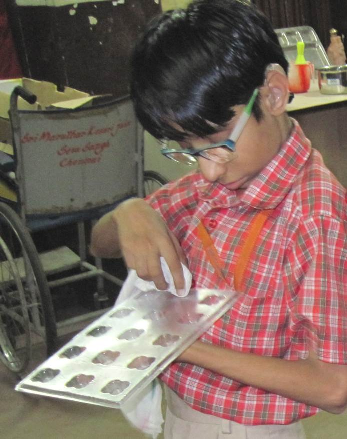 A boy with glasses and hearing aids prepares a pan for the chocolates