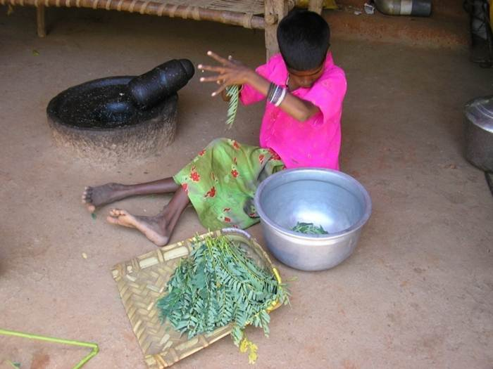 A girl prepares vegetables for cooking.