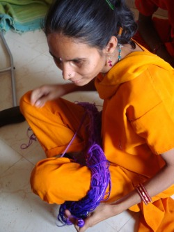 Photo of young woman winding a skein of purple yarn