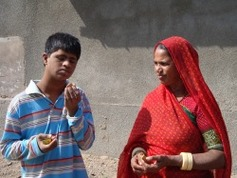 Harish examines a small object in his hand while his mother looks on.