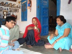 Photo of Harish sitting with his mother and Vimal Thawani of BPA.