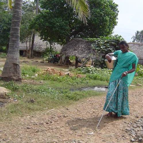 A young woman carries water with one hand and uses a cane with the other.