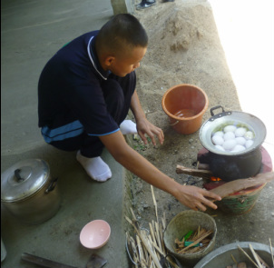 This young man is cooking in the traditional style over a small fire.
